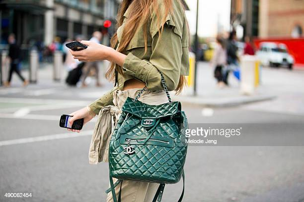 A showgoer wears a green outfit with a leather green Chanel backpack as a purse during London Fashion Week Spring Summer 2016 at Kings Cross on...