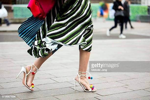 A showgoer wears quirky greenstriped skirt and white heels with pompoms at the Mary Katrantzou show at 1 Granary Square during London Fashion Week...