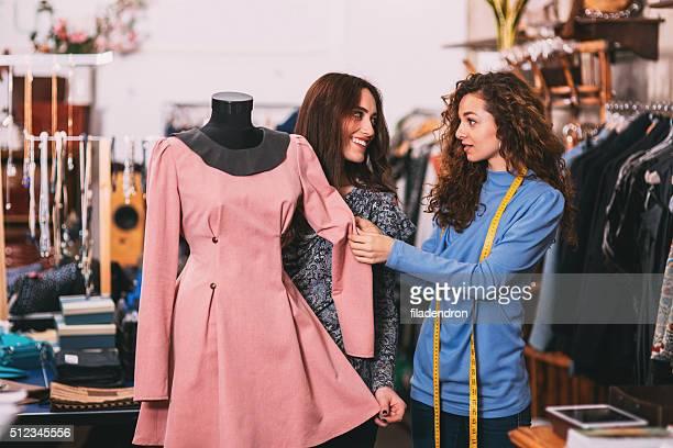 Zeigt ein Kleid an einem Kunden