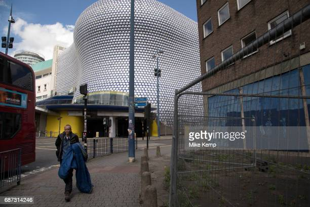 Showing the gap between rich and poor a homeless man carrying his sleeping bag past the modern landmark architecture of the Selfridges Building in...