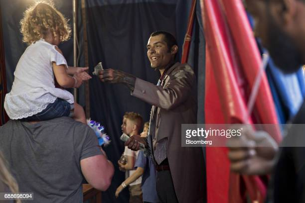 A showman collects money from a child during a performance in the World of Wonders tent during the Dreamland Amusements carnival in the parking lot...