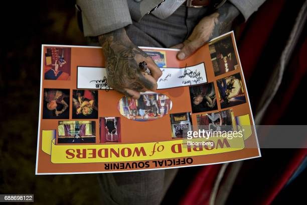 A showman signs a souvenir poster in the World of Wonders tent during the Dreamland Amusements carnival in the parking lot of the Neshaminy Mall in...