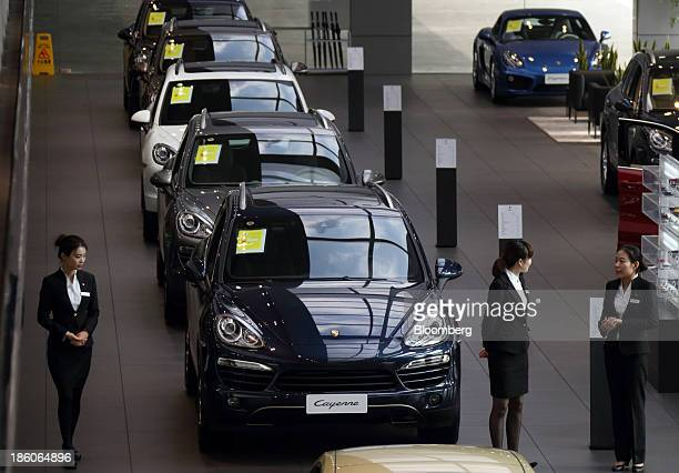 Showroom employees stand beside a Porsche AG Cayenne sport utility vehicle at the Porsche Centre Shanghai Minhang showroom in Shanghai China on...