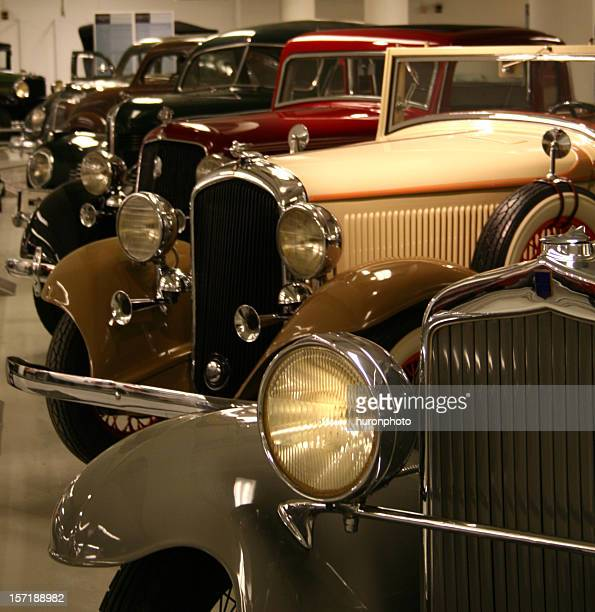 A showroom with a collection of vintage cars