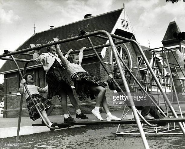 Shows children playing in a school playground on an aframe slideswing in Melbourne