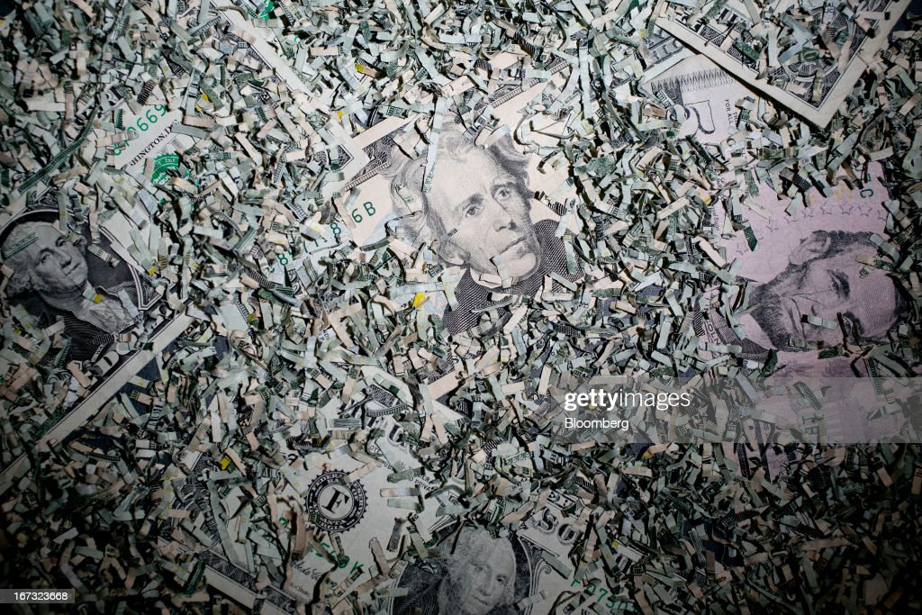 Shredded currency surrounds U.S. dollar bills in Washington, D.C., U.S., on Wednesday, April 24, 2013. The S&P 500 has surged 134 percent from a 12-year low in 2009 as corporate earnings beat estimates and the Federal Reserve embarked on three rounds of bond purchases to stimulate the economy. Photographer: Andrew Harrer/Bloomberg via Getty Images