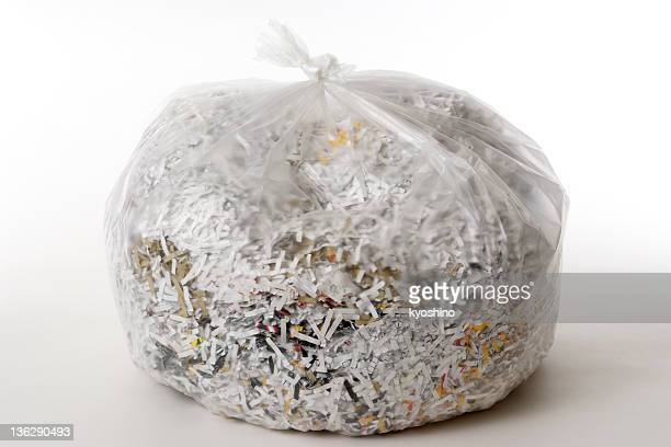 Shredded documents in garbage bag on white background