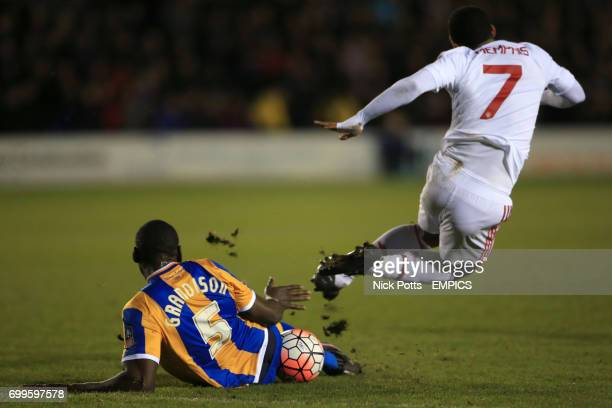 Shrewsbury Town's Jermaine Grandison tackles Manchester United's Memphis Depay