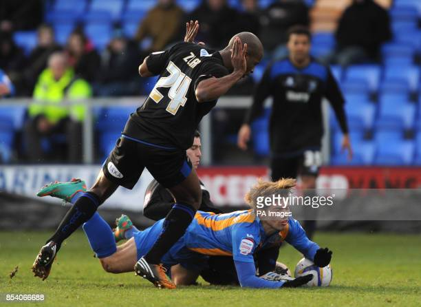 Shrewsbury Town's Tom Bradshaw goes to ground after being challenged by Bury's Steven Schumacher and Stephane Zubar during the npower Football League...