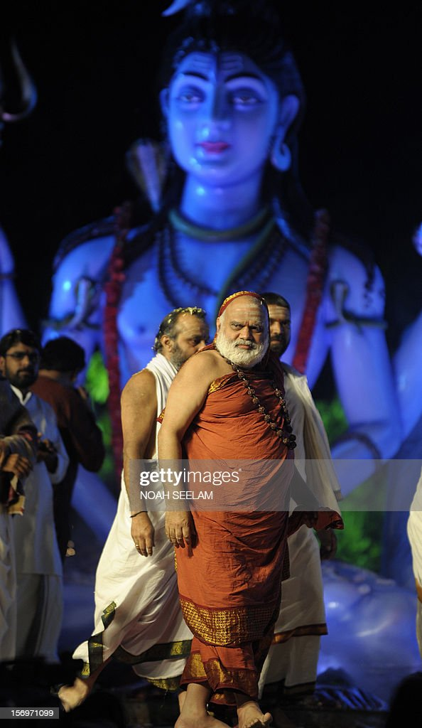 Shri Chandrasekara Bharathi Theertha Swamigal of Sringeri (C) arrives to grace the event as Indian Hindu devotees perform a ritual by lighting diyas - earthen lamps - on the occasion of Karthika month in Hyderabad on November 26, 2012. Karthika month is one of the most auspicious months in the lunar calendar which begins on the day after Diwali, the Festival of Lights and ends after 30 days. It is considered very sacred by the devotees of Lord Shiva and Lord Vishnu. AFP PHOTO / Noah SEELAM