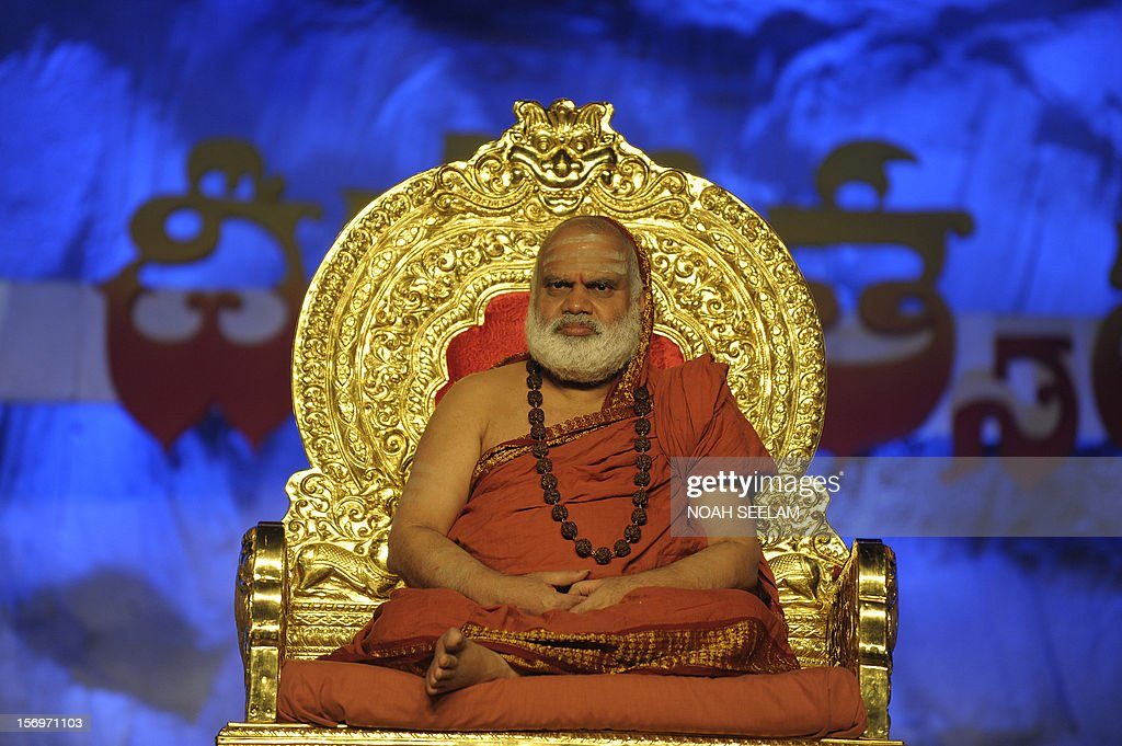 Shri Chandrasekara Bharathi Theertha Swamigal of Sringeri graces the event as Indian Hindu devotees perform a ritual by lighting diyas - earthen lamps - on the occasion of Karthika month in Hyderabad on November 26, 2012. Karthika month is one of the most auspicious months in the lunar calendar which begins on the day after Diwali, the Festival of Lights and ends after 30 days. It is considered very sacred by the devotees of Lord Shiva and Lord Vishnu. AFP PHOTO / Noah SEELAM