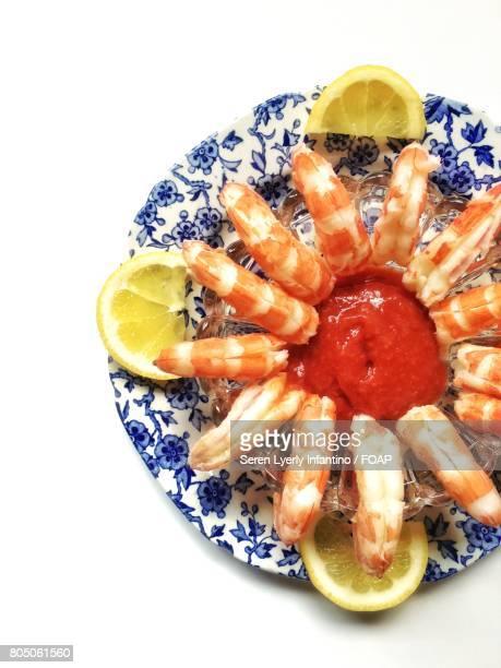 Shrimp cocktail with lemon on white background