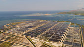 shrimp farm, prawn farming with with aerator pump oxygenation water near ocean. aerial view fish farm with ponds growing fish and shrimp and other seafood. Fish hatchery pond aerial view aquaculture b