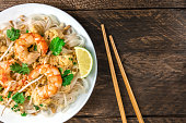 A closeup photo of a Shrimp Pad Thai, traditional Tailandese dish with stir fried rice noodles, shot from above on a rustic texture with chopsticks and copy space
