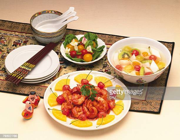 Shrimp with chili sauce, salad and almond jelly, high angle view, orange background