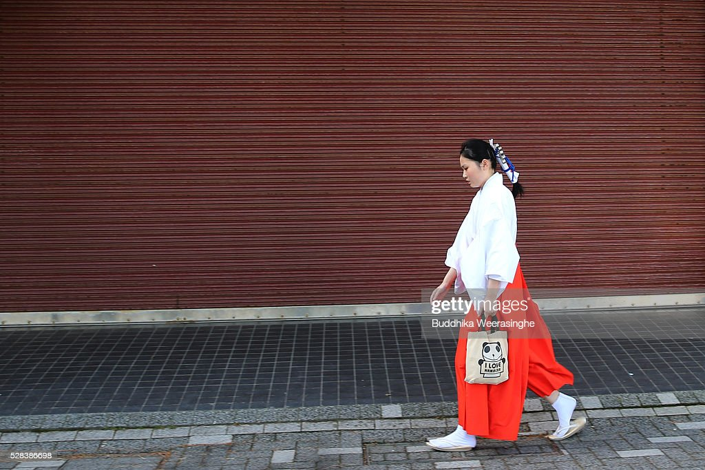 A Shrine maiden walks as arrive to attend the Oshimenawahari ceremony at Futami Okitama Shrine on May 5, 2016 in Ise, Japan. The Oshimenawahari ceremony is held three times a year to exchange the 35 meters long heavy rope made of rice straw that connects the sacred Couple Rock - one small, one big. The Couple Rock serves as a gate to the Okitama Shrine, dedicated to the god Sarutahiko and goddess Ukanomitama from Japanese myth.