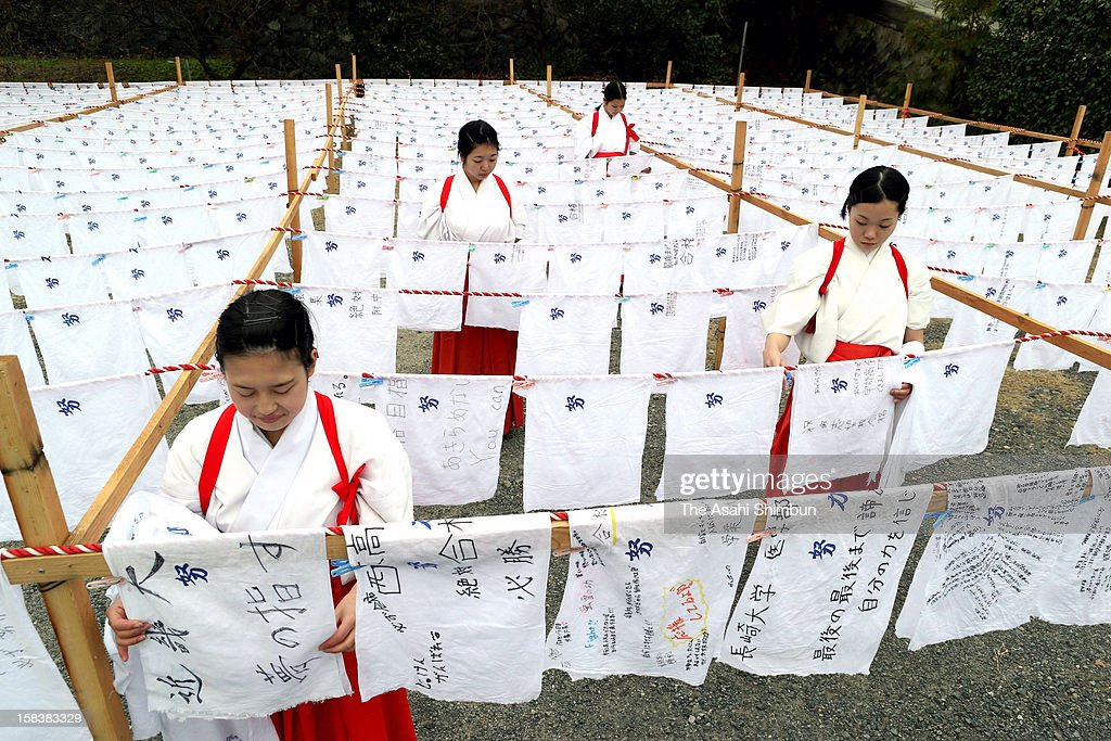Shrine maidens hungs bundles dyeing 'Effort' at Hofu Tenmangu shrine on December 14, 2012 in Hofu, Yamaguchi, Japan. The 3,500 bundles, returned from the students who passes university entrance examinations this spring, will be distributed to those wish to pass their exams this year.