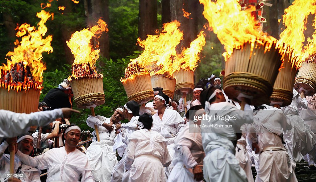 Shrine parishioners hold big memorial torches to purify the path for portable shrines during Kumano Nachi Fire Festival on July 14, 2014 in Nachikatsuura, Wakayama, Japan. The festival, held on July 14 every year, originated 1,500 years ago and attracts 10,000 people.