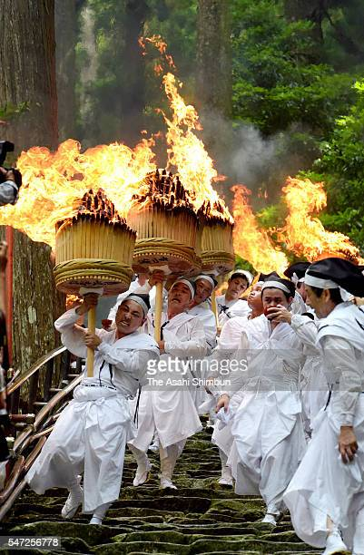 Shrine parishioners hold big memorial torches to purify the path for portable shrines during the Ogi Festival better known as the Kumano Nachi Fire...