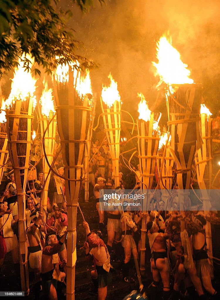Shrine parishioners holding fire-burnt torches during the Kurama Fire Festival at Yuri Shrine on October 22, 2012 in Kyoto, Japan. The participants parade through the community carrying some 500 torches which measure five meters long and weigh 50kg. The origin of this tradition dates back to the Heian Period when village members would build a bonfire to greet the deity of the shrine.