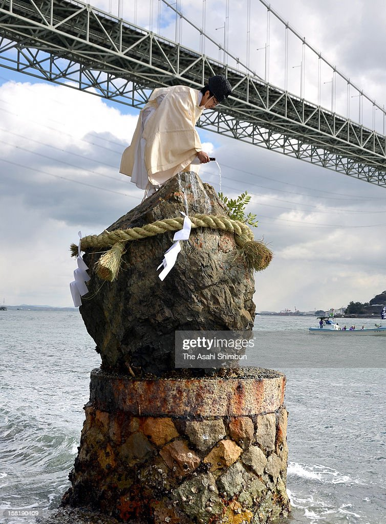 A Shrine priest pours Japanese sake on the sacred rock as a part of Shimenawa matsuri, traditional ritual carried out on the shore of Shimonoseki in hope of good catch and safety at sea on December 10, 2012 in Shimonoseki, Yamaguchi, Japan.