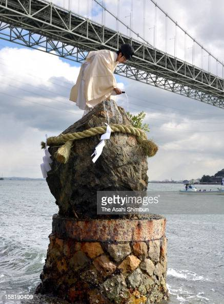 A Shrine priest pours Japanese sake on the sacred rock as a part of Shimenawa matsuri traditional ritual carried out on the shore of Shimonoseki in...