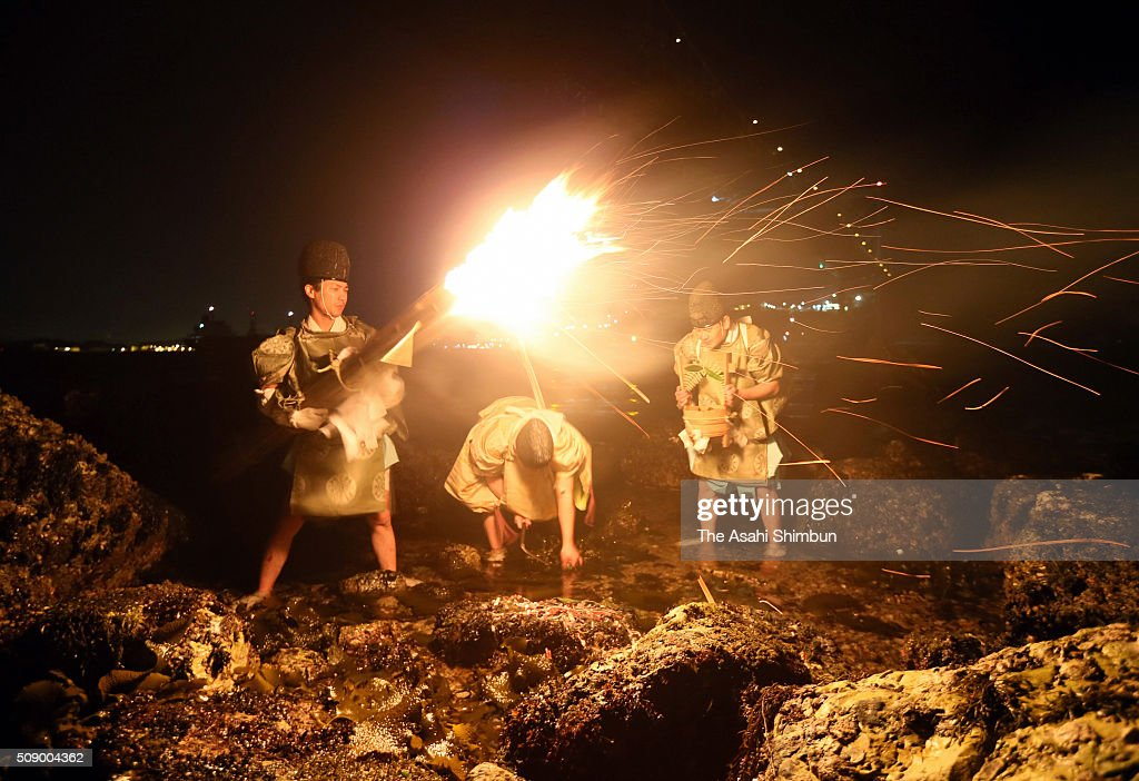 Shrine priests crop seaweeds under a flaming torch during the Mekari (Seaweed Harvesting) Ritual at Mekari Shrine on February 8, 2016 in Kitakyushu, Fukuoka, Japan. The ritual, taken place at the same time with both sides of the Kanmon Strait, is to pray for good harvest of seaweed and marine safety.