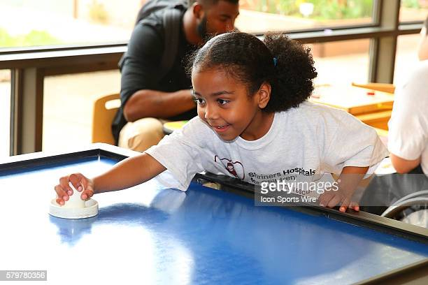 Shriners Hospital Patient Nevaeh Martinez plays air hockey at the Shriners Childrens Hospital in Chicago The event brought 19 2015 NFL Draft Picks to...