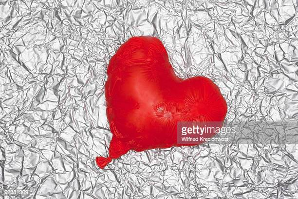 shrinking heart balloon on silver background
