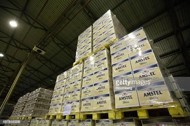 Shrinkwrapped cases Amstel Weiss beer bottles sit on wooden pallets inside the warehouse at the Heineken NV brewery in Saint Petersburg Russia on...