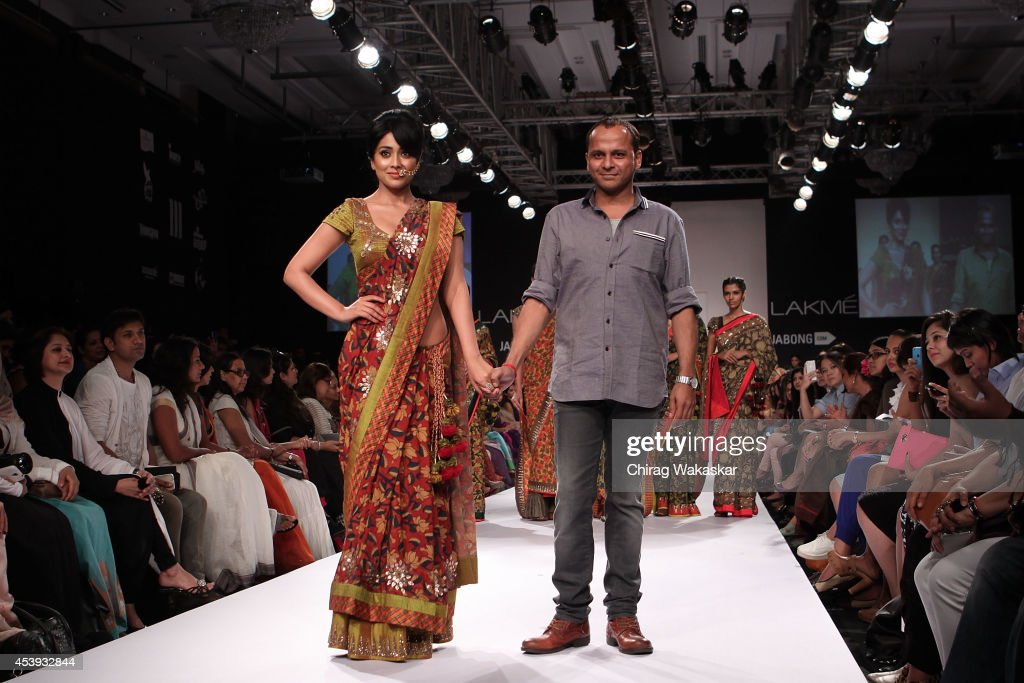 <a gi-track='captionPersonalityLinkClicked' href=/galleries/search?phrase=Shriya+Saran&family=editorial&specificpeople=5378055 ng-click='$event.stopPropagation()'>Shriya Saran</a> (L) walks the runway with Sashikant Naidu (R) during day 2 of Lakme Fashion Week Winter/Festive 2014 at The Palladium Hotel on August 21, 2014 in Mumbai, India.