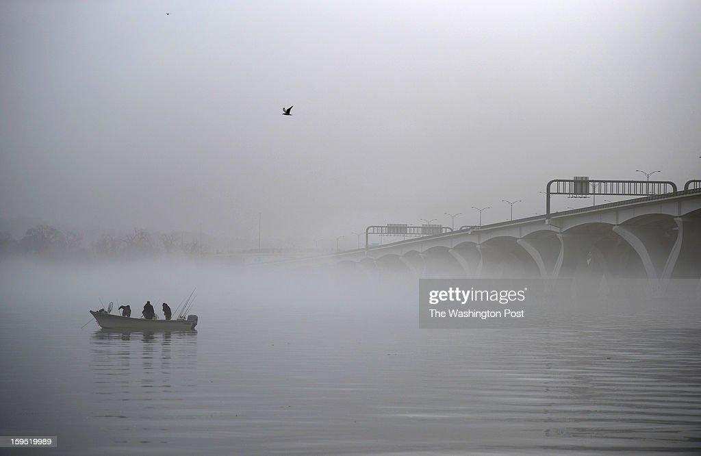 Shrouded in fog, people fish near the Woodrow Wilson Memorial Bridge on the Potomac River on Saturday January 12, 2013 in Alexandria, VA.
