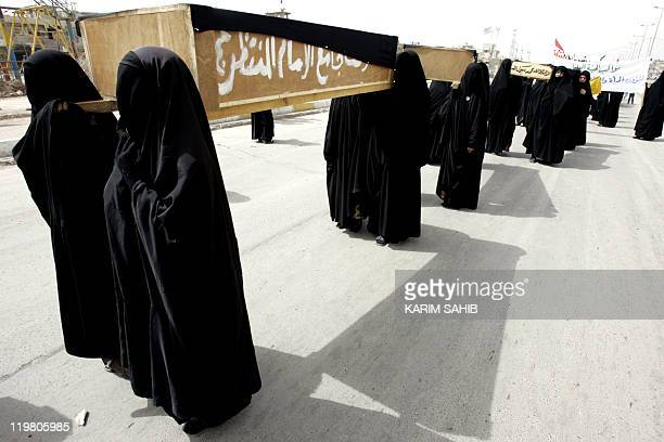 Shrouded in the traditional black Shiite Muslim headtotoe chador Iraqi women carry three mock coffins one marked 'women and children of Lebanon'...
