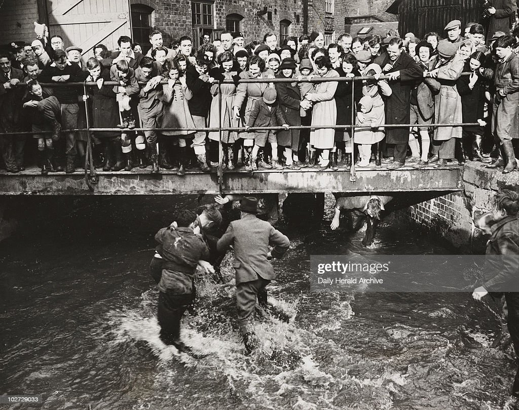 'Shrovetide football at Ashbourne', 1950. A photograph of players fighting their way along Henmore Brook during the Shrovetide football match in Ashbourne, Derbyshire, in 1950. Shrovetide football in Ashbourne has taken place on Shrove Tuesday and Ash Wednesday annually for hundreds of years. As many as several thousand residents of Ashbourne compete, divided into two teams - the Up'ards (those who were born on the north side of Henmore Brook), against the Down'ards (born on the South side).