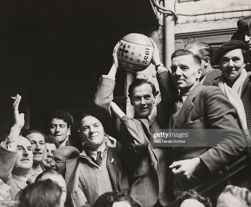 'Shrovetide Football at Ashbourne', 1952. A photograph of the Duke of Devonshire, holding aloft the hand-painted football which he 'turned up' to start the 1952 Shrovetide football match in Ashbourne, Derbyshire. Shrovetide football in Ashbourne has taken place on Shrove Tuesday and Ash Wednesday annually for hundreds of years. As many as several thousand residents of Ashbourne compete, divided into two teams - the Up'ards (those who were born on the north side of Henmore Brook), against the Down'ards (born on the South side).
