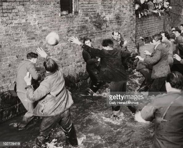'Shrovetide Football at Ashbourne' 26 February 1952 Gelatin silver print A photograph of players fighting for possession of the ball in Henmore Brook...