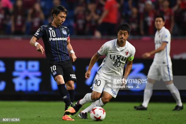 Shu Kurata of Gamba Osaka and Mitsuo Ogasawara of Kashima Antlers compete for the ball during the JLeague J1 match between Gamba Osaka and Kashima...