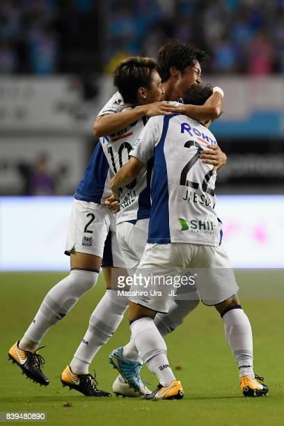 Shu Kurata of Gamba Osaka celebrates scoring the opening goal with his team mates Genta Miura and Oh Jae Suk during the JLeague J1 match between...