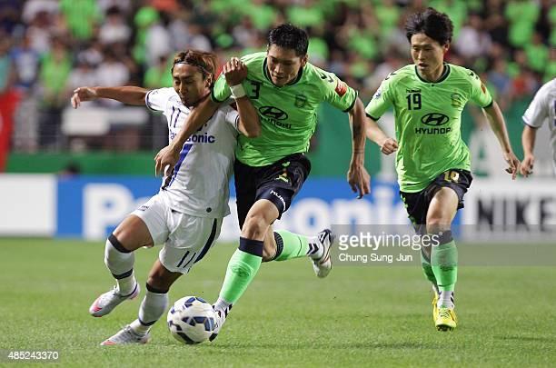 Shu Kurata of Gamba Osaka compete for the ball with Kim HyungIl of Jeonbuk Hyundai Motors during the AFC Champions League quarter final match between...