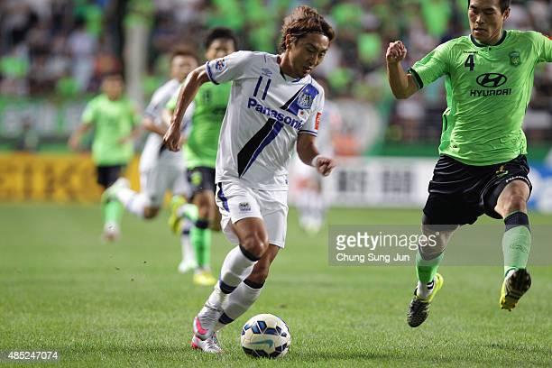 Shu Kurata of Gamba Osaka compete for the ball with Kim KeeHee of Jeonbuk Hyundai Motors during the AFC Champions League quarter final match between...