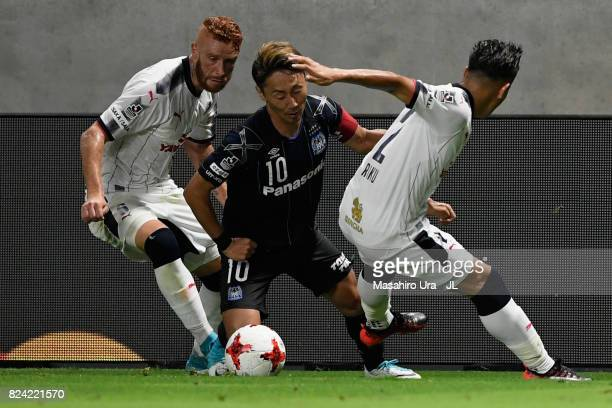 Shu Kurata of Gamba Osaka competes for the ball against Souza and Riku Matsuda of Cerezo Osaka during the JLeague J1 match between Gamba Osaka and...