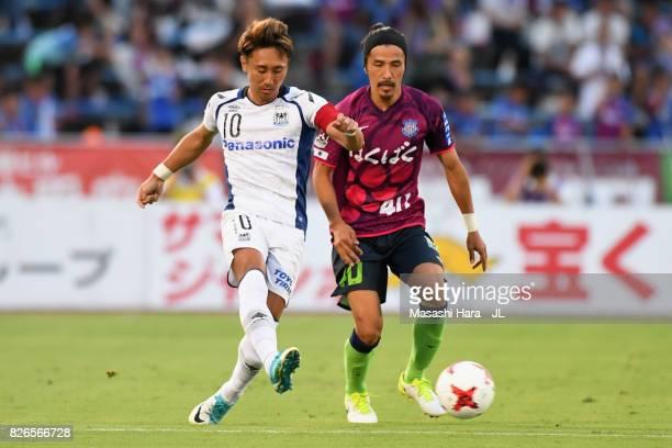Shu Kurata of Gamba Osaka controls the ball under pressure of Shohei Ogura of Ventforet Kofu during the JLeague J1 match between Ventforet Kofu and...
