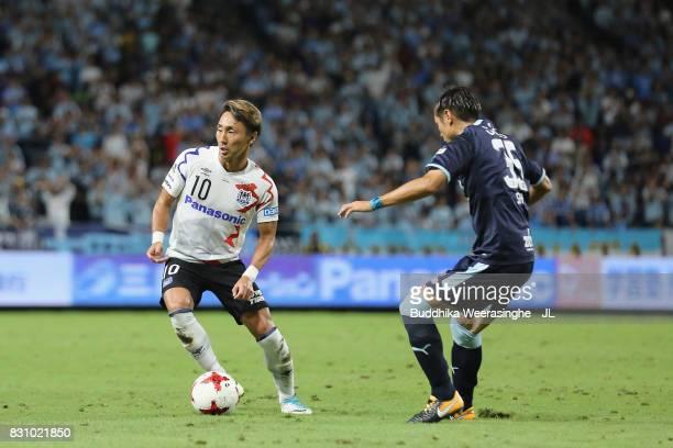 Shu Kurata of Gamba Osaka controls the ball under pressure of Shun Morishita of Jubilo Iwata during the JLeague J1 match between Gamba Osaka and...
