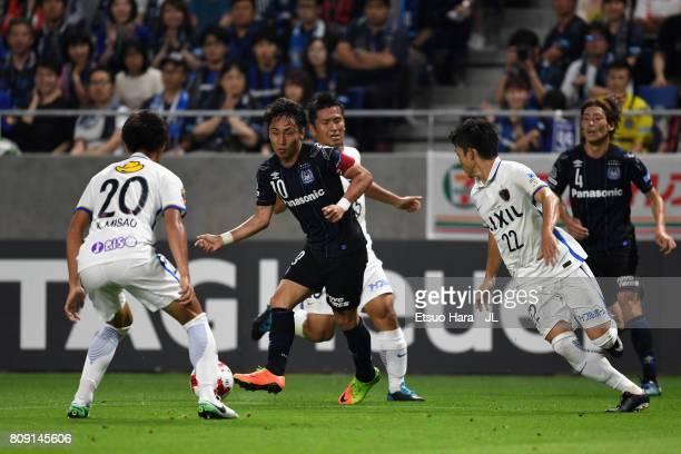Shu Kurata of Gamba Osaka controls the ball under pressure of Kawasaki Frontale defense during the JLeague J1 match between Gamba Osaka and Kashima...