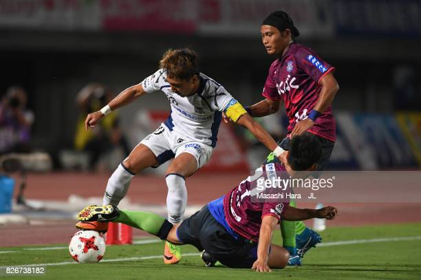 Shu Kurata of Gamba Osaka is challenged by Shohei Abe and Yusuke Tanaka of Ventforet Kofu during the JLeague J1 match between Ventforet Kofu and...