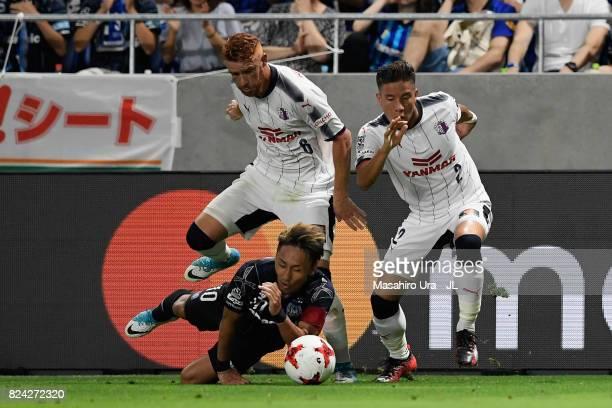Shu Kurata of Gamba Osaka is challenged by Souza and Riku Matsuda of Cerezo Osaka during the JLeague J1 match between Gamba Osaka and Cerezo Osaka at...