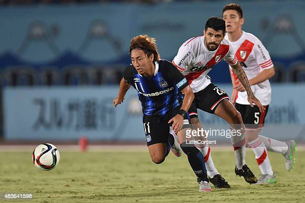Shu Kurata of Gamba Osaka runs for the ball as he is challenged by Luis Gonzalez of River Plate during a match between Gamba Osaka and River Plate as...