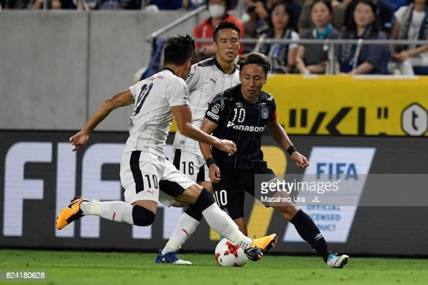 Shu Kurata of Gamba Osaka takes on Kota Mizunuma and Hotaru Yamaguchi of Cerezo Osaka during the JLeague J1 match between Gamba Osaka and Cerezo...
