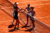 Shuai Peng of China and SuWei Hsieh of Chinese Taipei shake hands with Sara Errani of Italy and Roberta Vinci of Italy after their women's doubles...