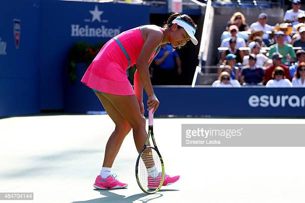 Shuai Peng of China grabs her leg after a play against Caroline Wozniacki of Denmark during their women's singles semifinal match on Day Twelve of...
